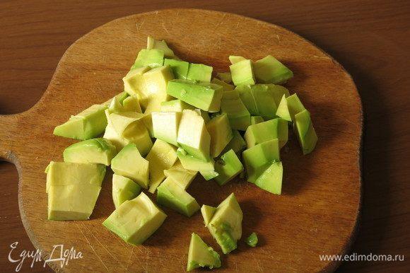 Нарезаем очищенное авокадо.