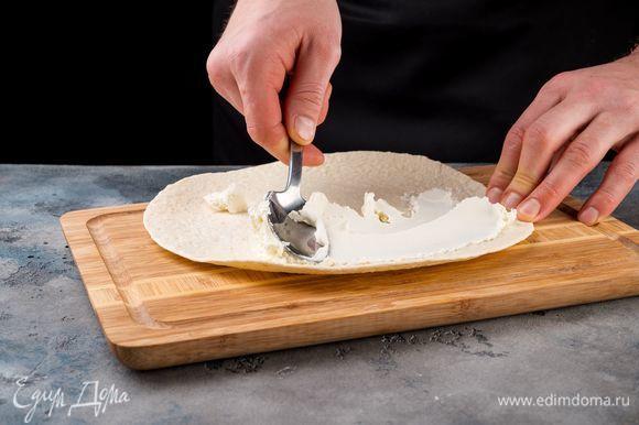 На рабочей поверхности разверните лаваш. Смажьте его равномерно сливочным сыром.