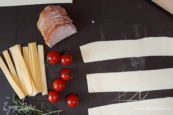 Слоеное тесто немного размораживаем и раскатываем, разрезаем на полоски шириной около 7 см.