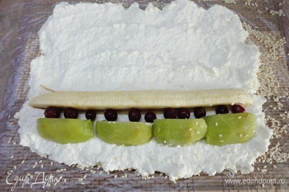 Коврик застелите пленкой и посыпьте кунжутом или кокосовой стружкой (у нас, в семье любителей, таковой не нашлось), выложите творожную массу с помощью мокрой ложки, затем по краю расположите фрукты, а также какую-нибудь красненькую ягоду. У меня брусника. Можно гранат, смородину и т. п.