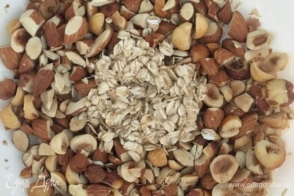 Орехи порубить не очень мелко. Соединить в миске рубленые орехи с овсяными хлопьями. Добавить кокосовое масло и кленовый сироп, все перемешать. Овсяно-ореховый крамбл для полезной сладости готов, все очень легко и просто.