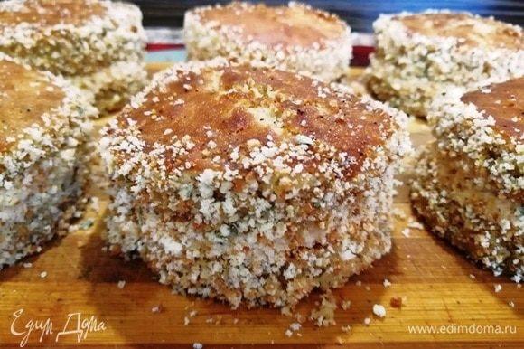 Обваливаем бока пирожных в бисквитной крошке.