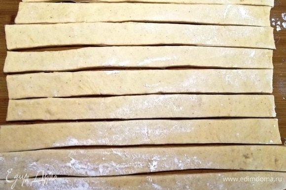 Половину теста раскатываем в тонкий пласт и нарезаем полосками около 2 см.
