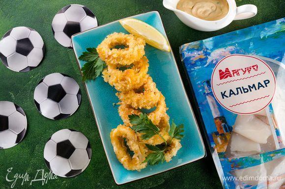 Подаем жареные кольца кальмаров в кляре с приготовленным сливочным соусом. Всем приятного аппетита! Ваши гости точно будут болеть за эту закуску!