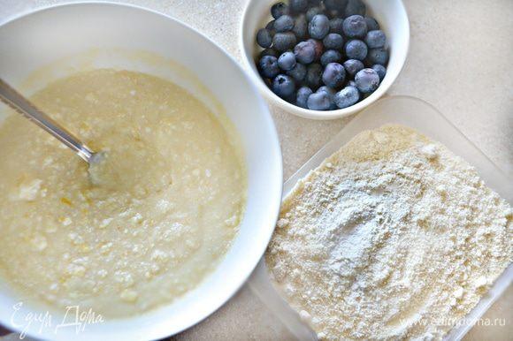 Просейте муку вместе с миндальной и разрыхлителем, добавляйте в творожную массу в несколько приемов. Чернику промойте, обсушите и аккуратно вмешайте в тесто.