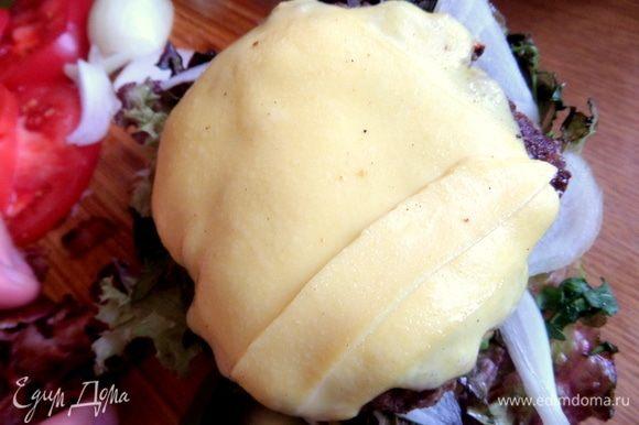 Переносим на салат готовую котлетку с сыром. Сверху — кусочки бекона.
