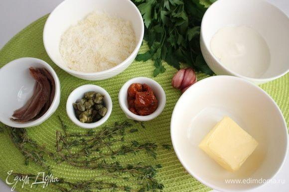 Приготовить все необходимое для начинки. Чеснок почистить. Сыр натереть на мелкой терке, вяленые томаты в масле нарезать на небольшие кусочки. К размягченному при комнатной температуре маслу добавить чеснок, пропущенный через пресс, белый свежемолотый перец, соль, перемешать вилкой.
