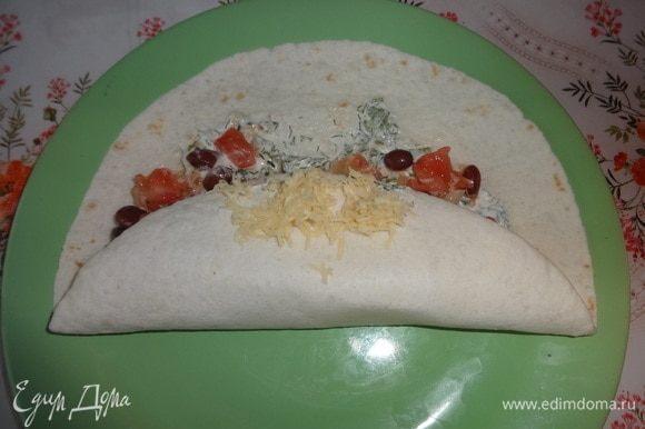 Загнуть один край тортильи на начинку, посыпать небольшим количеством сыра. Завернуть второй край лепешки внахлест на первый.