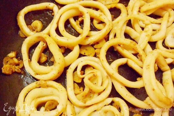 Добавить соль и черный свежемолотый перец. Жарить, непрерывно помешивая, не более 4 минут. Самое главное — не передержать кальмары на огне, иначе они станут просто резиновыми!