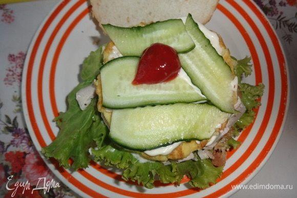 Омлет смазать 1/2 ст. л. майонеза, выложить на него пластины огурца. Огурцы смазать оставшимся кетчупом и накрыть второй половиной булочки. Таким же образом собрать два других бургера.