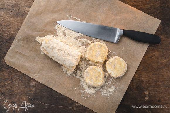 Рабочую поверхность посыпьте оставшейся кедровой мукой. Раскатайте тесто в колбаску диаметром примерно 5 см. Нарежьте ее кружками толщиной 1,5 см. Обваляйте каждый сырник в муке.