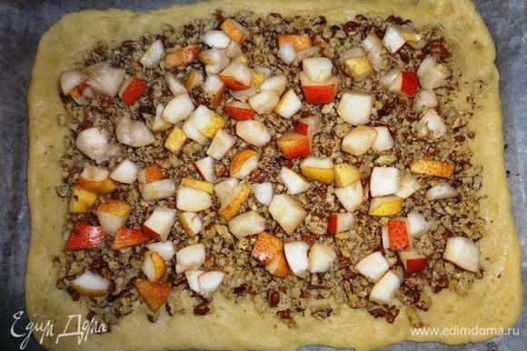 На орехи выложить слой нарезанных груш.