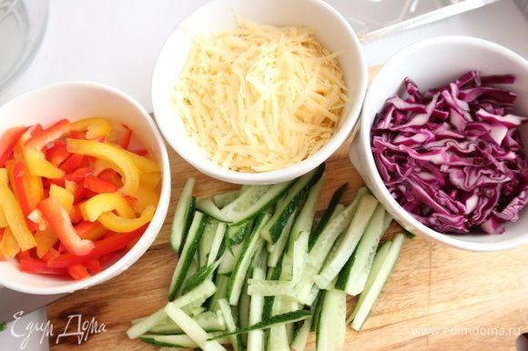 Перец нарезать тонкими пластинами, краснокочанную капусту нарезать тонко, огурцы — тонкой соломкой, сыр натереть на крупной терке.