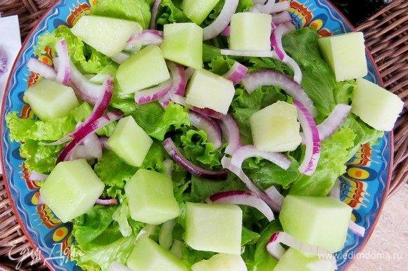 Дыню также нарезать кубиками и равномерно выложить на листья салата.