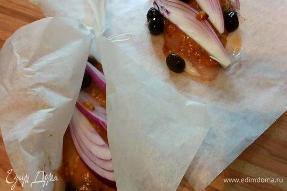 Маленький лук очистить и нарезать на стрелки. Выложить на курицу лук и маслины. Свернуть пергамент пакетиком, завязать кончики.