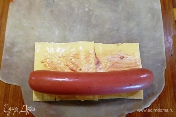 Смазываем сыр небольшим количеством майонеза и кетчупа. Сверху укладываем сосиску.