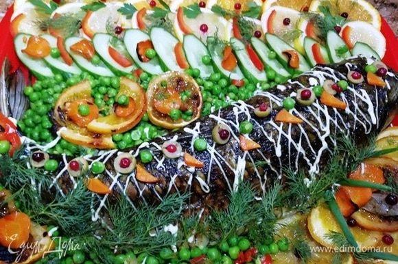 Подаем белого амура с запеченными и свежими овощами, украсив зеленью и майонезом.
