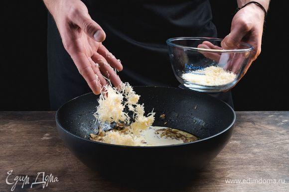 Добавьте к грибам сливки и пармезан, специи, хорошо перемешайте и доведите до кипения.