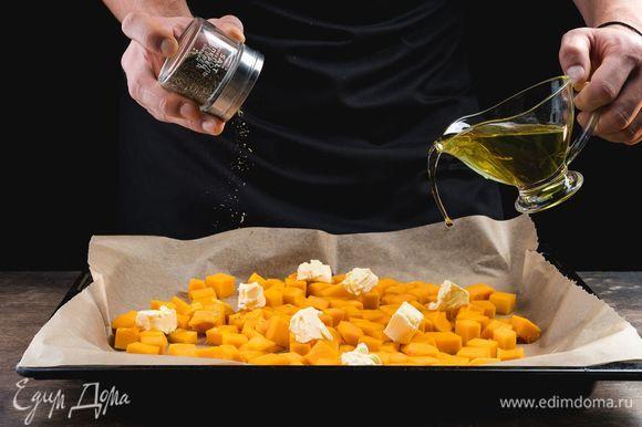 Застелите противень бумагой для выпечки, выложите тыкву, посолите, поперчите, посыпьте орегано, сбрызните оливковым маслом и положите кусочки сливочного масла. Запекайте тыкву 15 минут при 200°С.