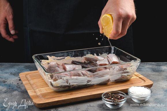 В смазанную маслом форму для запекания выложите рыбу и сбрызните лимонным соком. Затем посыпьте специями и оставьте мариноваться.