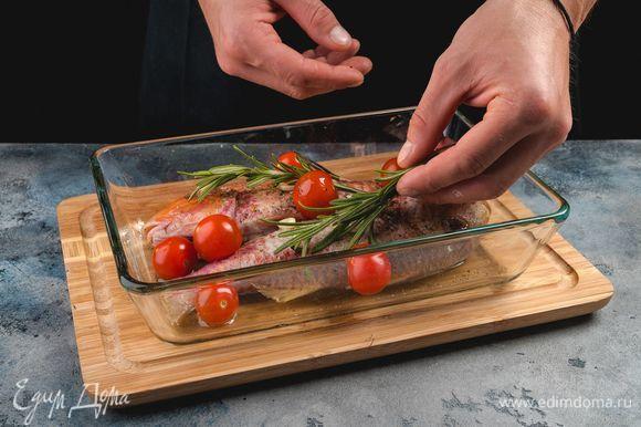 Сбрызните рыбу оливковым маслом и выложите на нее порубленный чеснок и веточки розмарина.