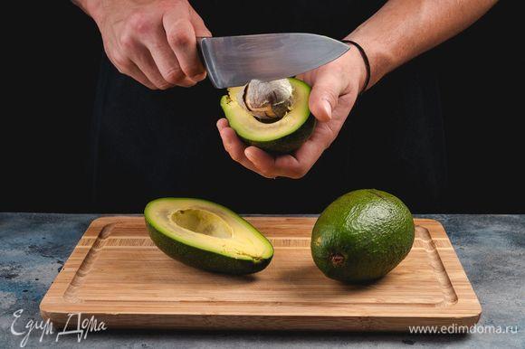 Вымойте авокадо, разрежьте пополам, достаньте косточки.