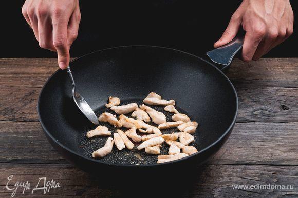 Разогрейте большую глубокую сковороду с маслом, обжарьте куриное филе ломтиками, чтобы оно стало светлым.