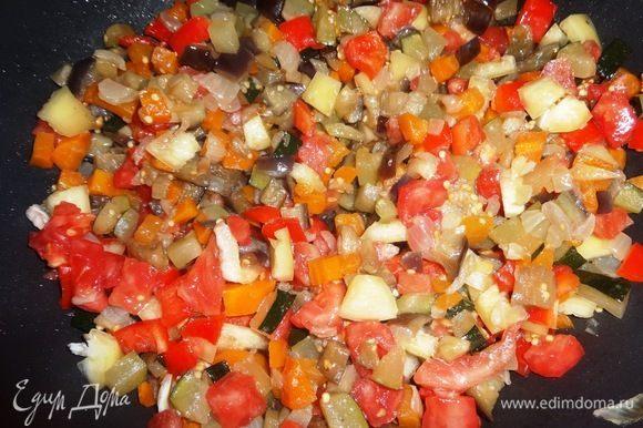 Добавить перец и помидор в сковороду к овощам, перемешать, жарить еще несколько минут, чтобы перец немного размягчился.