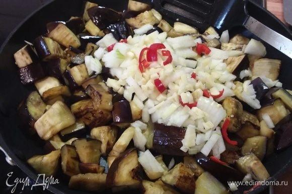 Разогреть масло в большой сковороде и обжарить баклажаны до золотистого цвета. Чаще мешайте, чтобы не подгорели. Добавить мелконарезанный лук, чеснок и перец чили, обжарить вместе еще минуту.
