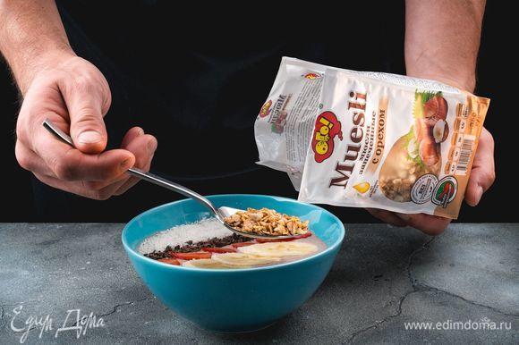 Украсьте смузи. Выложите полоску из запеченных мюсли с орехом ТМ «ОГО», рядом — полоску натертого шоколада, далее — дольки клубники, полоску из банановых кружочков и полоску кокосовой стружки.