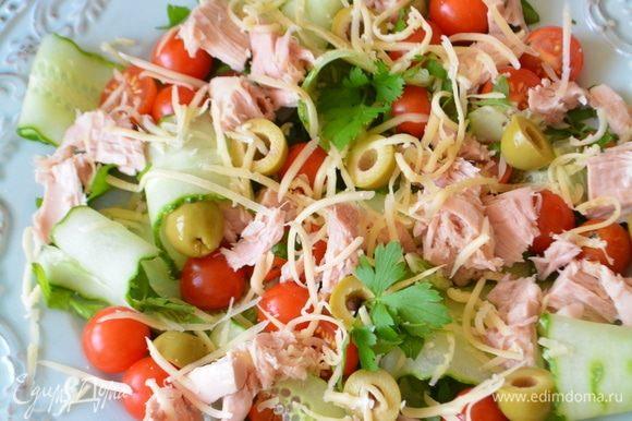 На широкое блюдо выкладываем первым слоем петрушку, дальше — помидоры, оливки, тунец, огурцы. Посыпаем все сыром и семенами темного и белого льна. Сдабриваем все свежемолотым перцем.