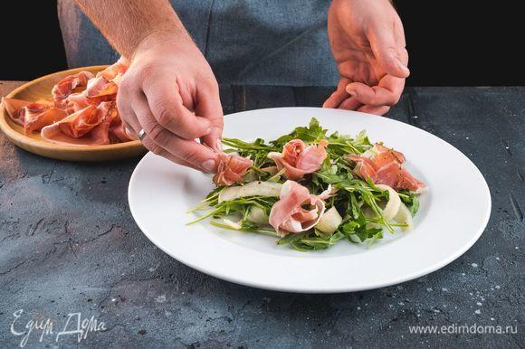 На сервировочную тарелку выложите руколу с грушей, сверху выложите ветчину.