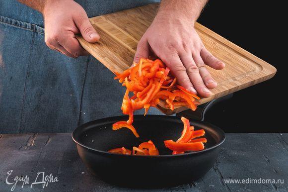 Обжарьте нарезанный перец на сковороде.