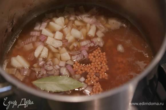 Чечевицу всыпать в кастрюлю, влить грибной бульон, добавить лук, чеснок, лавровый лист и отварить до готовности.
