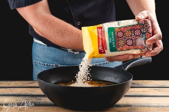 Засыпьте рис для плова «Националь», все перемешайте и залейте горячей водой так, чтобы она покрывала блюдо на 2–2,5 см. Накройте крышкой, уменьшите пламя до минимума, готовьте еще 20 минут.