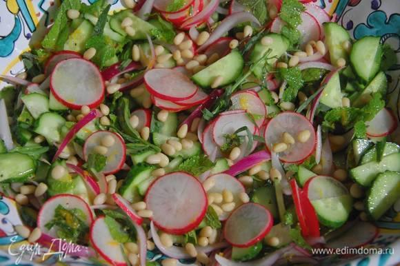 Полить салат заправкой, все перемешать и посыпать кедровыми орехами.