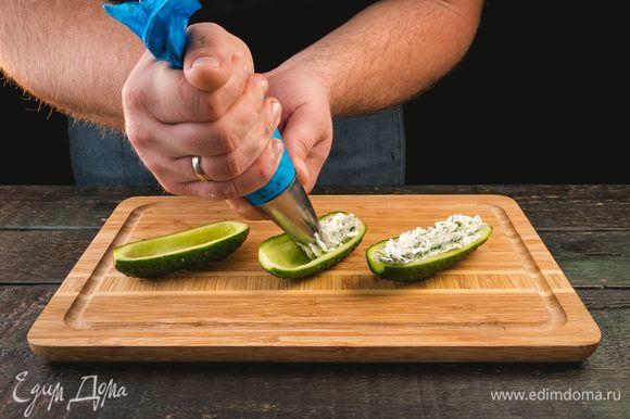 Огурец разрежьте пополам и сделайте лодочки, удалив сердцевины. В середину огуречной лодочки выложите начинку из сыра с зеленью.