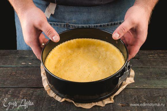 По прошествии указанного времени достаньте тесто, уложите в форму, формируя из краев теста бортики. Дно наколите вилкой в нескольких местах.