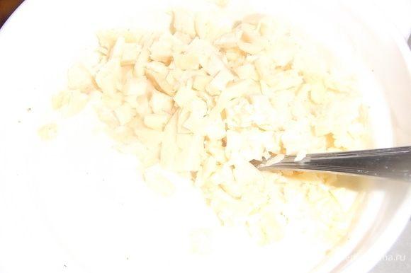 Яйца взболтать с оставшейся сметаной, солью и перцем. Добавить измельченный сыр. Перемешать.