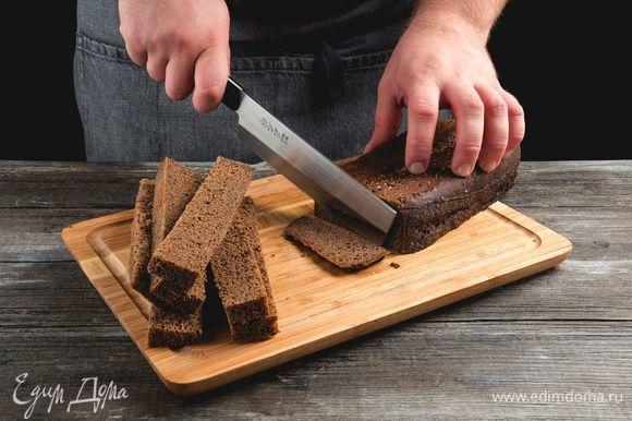 Возьмите буханку бородинского хлеба, лучше всего вчерашнего, срежьте все корочки, чтобы остался один мякиш. Нарежьте мякиш тостами толщиной 2 см, каждый разрежьте на 3–4 брусочка.