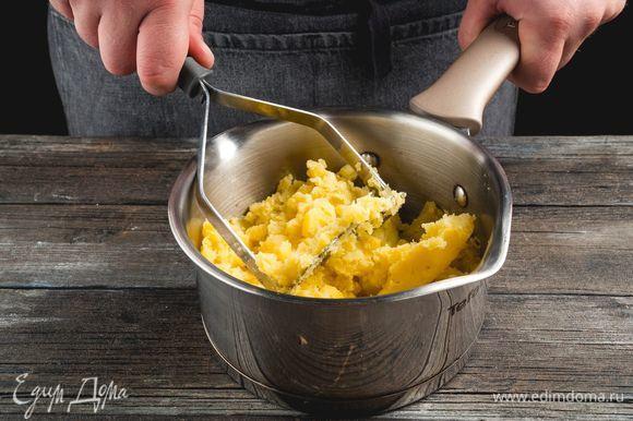 Отварите очищенные картофелины. Разомните толкушкой.