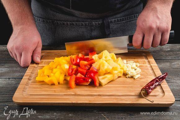 Нарежьте чеснок, перцы, ананасы, чили.