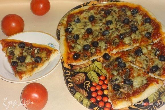 Готовую пиццу достать из духовки, выложить на блюдо. Разрезать на порции. Подавать горячей. Угощайтесь! Приятного аппетита!