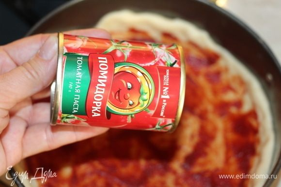 Готовое тесто разделить на 2 части. Первую часть раскатать и выложить в форму, формируя бортики. Смазать 1ст. л. томатной пасты ТМ «Помидорка».