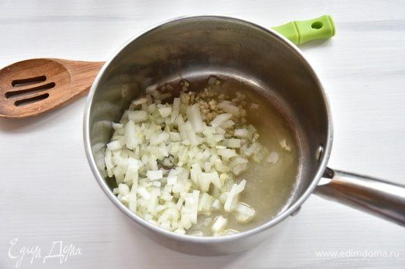 В сотейнике разогреть сливочное и оливковое масла, выложить лук и чеснок. Потомить овощи на медленном огне минуты 3.