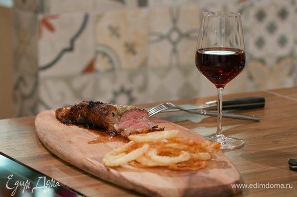 Из духовки достать мясо, полить его собственным соусом, который вытек в сковороду, и переложить на доску. Дать стейку отдохнуть 5 минут.