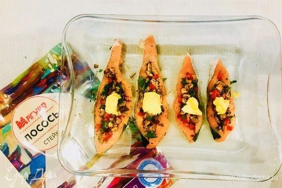 Получившейся смесью нафаршируйте филе лосося. Выложите лосось на предварительно смешанную маслом форму. На каждый кусочек положите по кусочку сливочного масла. Выпекайте в духовке при 180°C 20 минут.