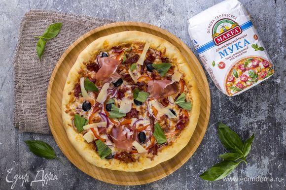 Запекайте пиццу в духовке, разогретой до 200°C, в течение 25 минут. На готовую пиццу выложите нарезанный слайсами пармезан, немного базилика и пармскую ветчину. Приятного аппетита!