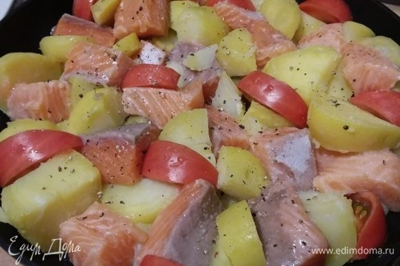 Картофель и лосося сложить в форму, в которой они будут запекаться. Между кусочками картофеля и лосося выложить половинки черри или дольки более крупных помидоров.
