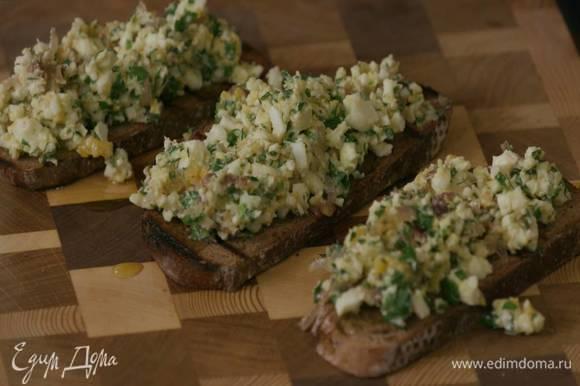 Второй зубчик чеснока разрезать пополам и натереть обжаренный хлеб, затем сбрызнуть оливковым маслом Extra Virgin и выложить на брускетту яичную начинку.